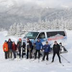 A group skis down from a SnowCoach tour